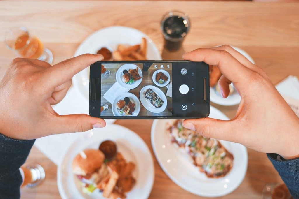 person taking a picture of food on cellphone