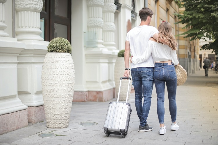ideal guest 2 - couple with luggage walking along the street